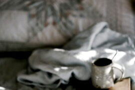a ruffled bed, a cup of tea