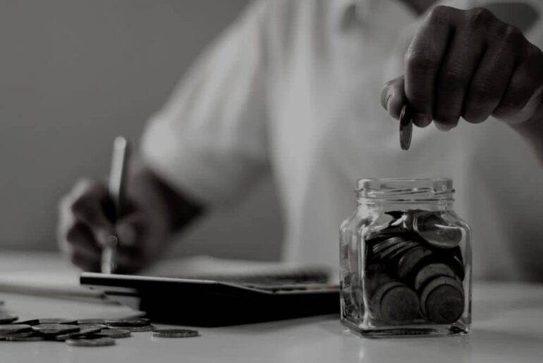 A person putting coins in a jar for saving