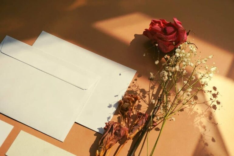2 white envelopes and flowers